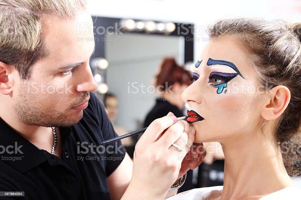 makeup artist applying lipstick on model lips with brush stock photo