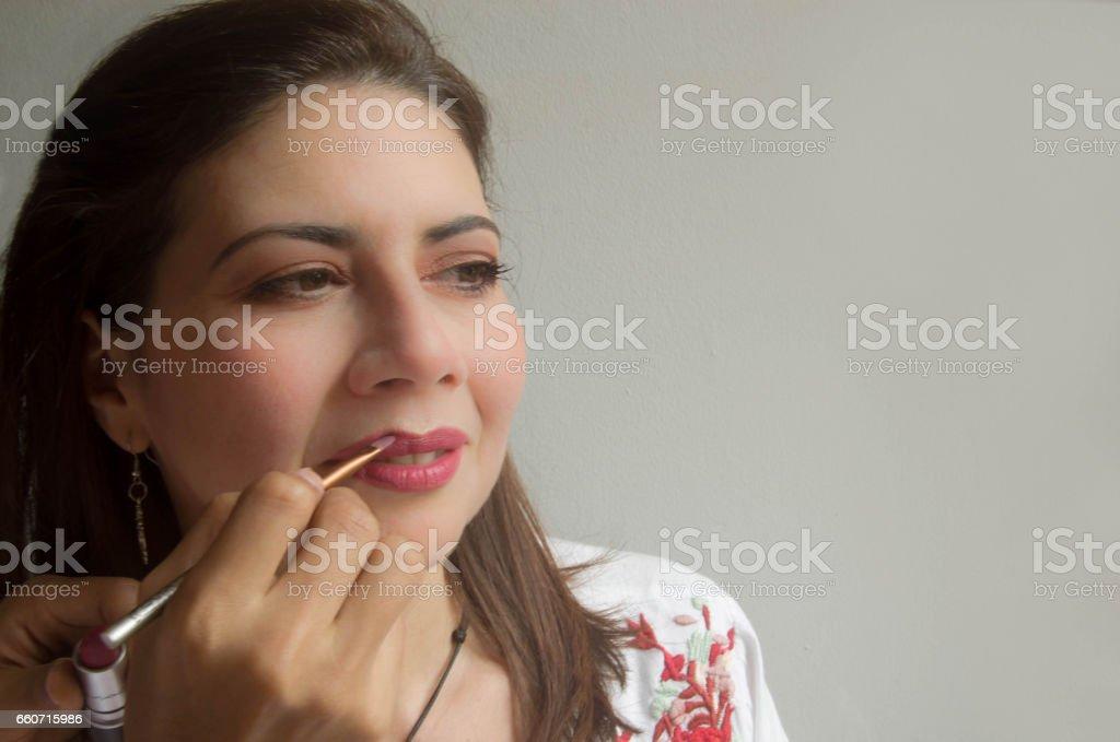 Makeup artist applying lipstick to women's lips, close-up stock photo