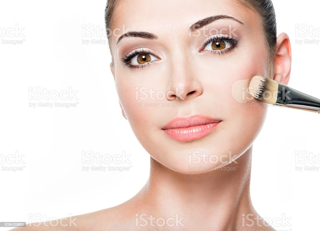 Makeup artist applying liquid tonal foundation  on the face stock photo