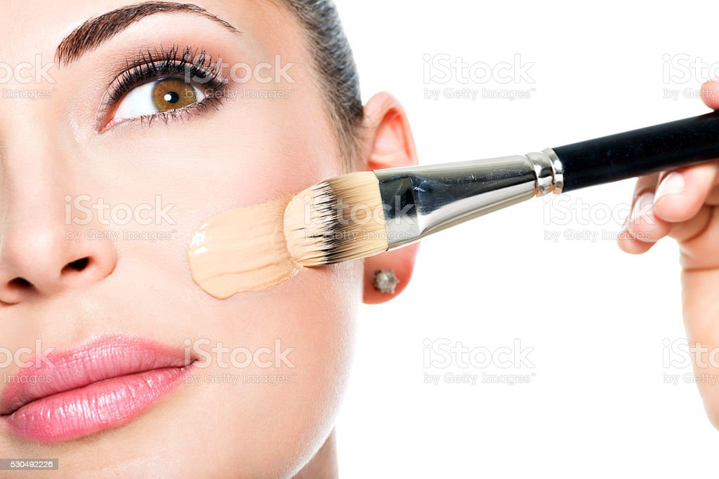 Makeup artist applying liquid tonal foundation  on the face stock photo