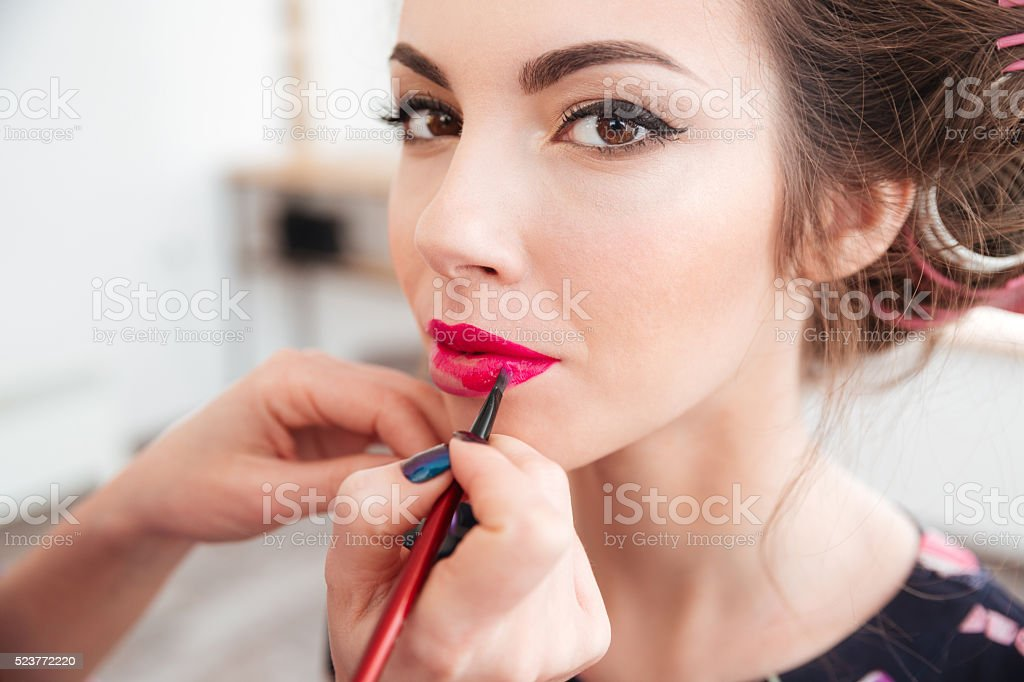 Makeup artist applying pink lipstick to lips of woman stock photo