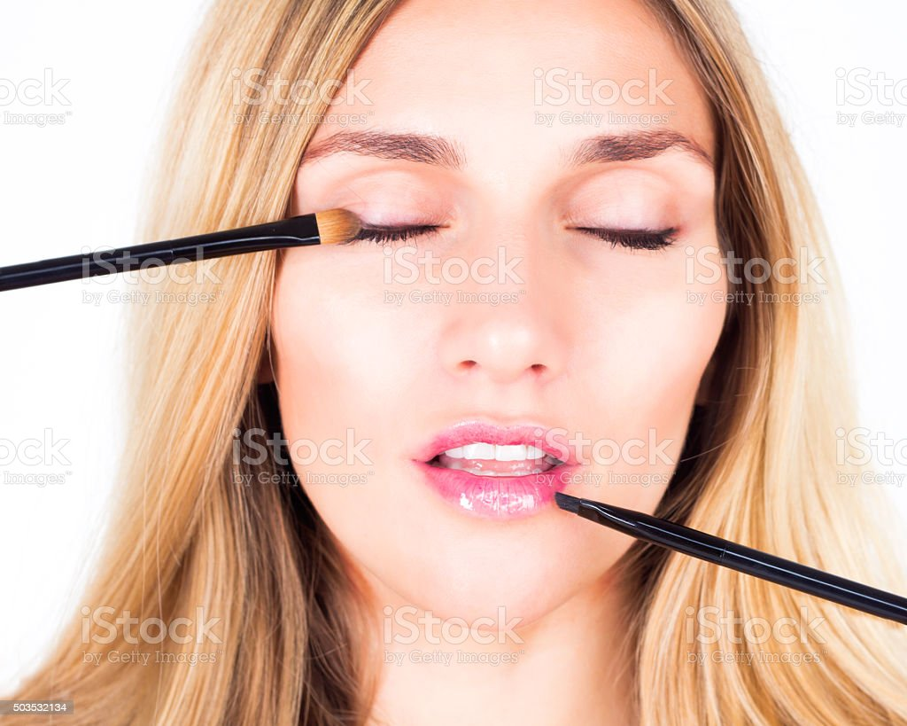 Make-up artist applying shadows and shine with cosmetic brushes stock photo