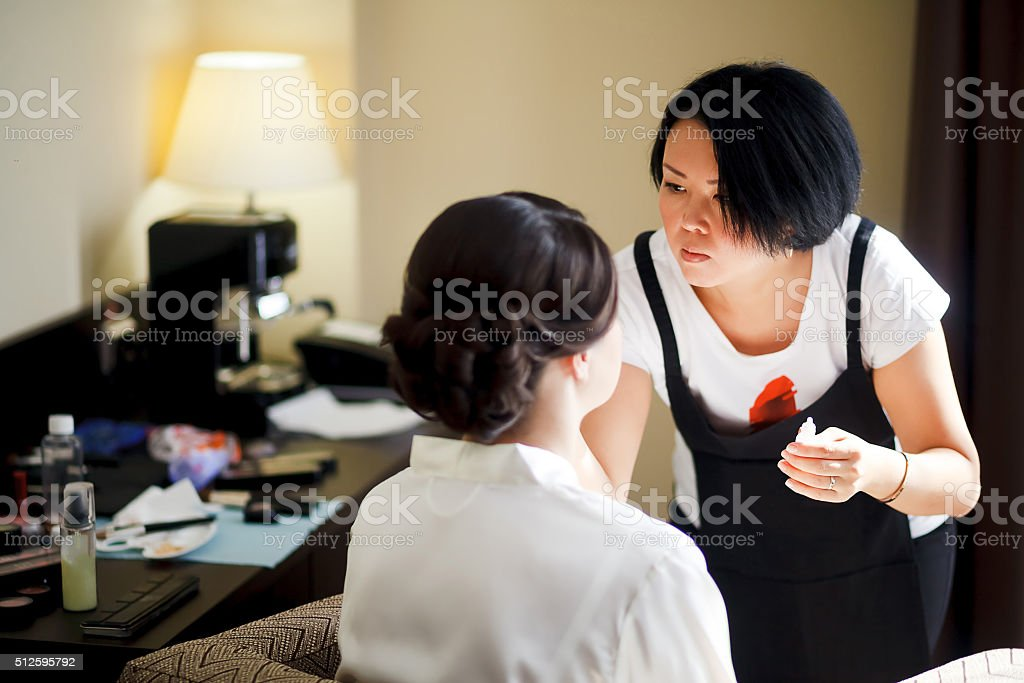 Makeup artist at work, asian woman doing makeup for bride stock photo