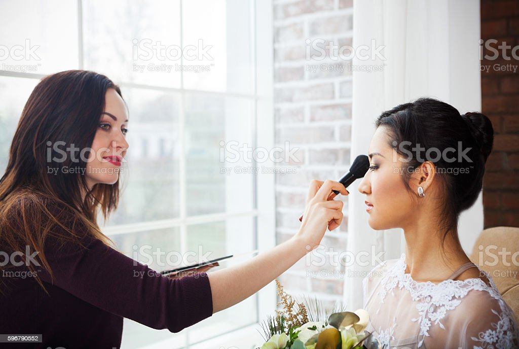 Make-up artist doing make up for young beautiful bride stock photo