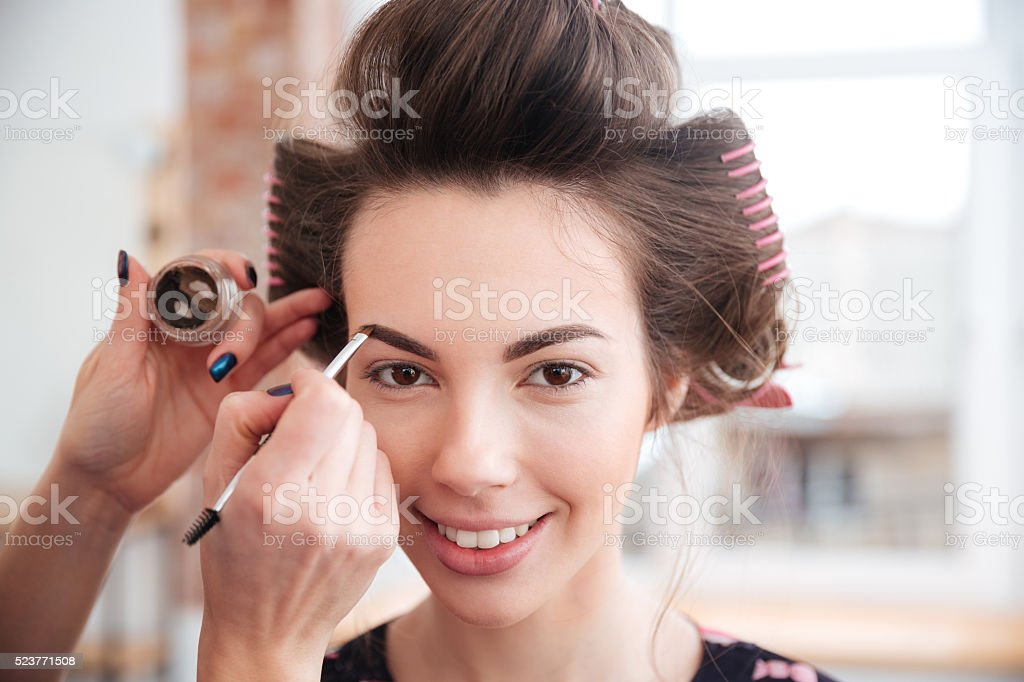 Makeup artist doing makeup to woman with curlers stock photo