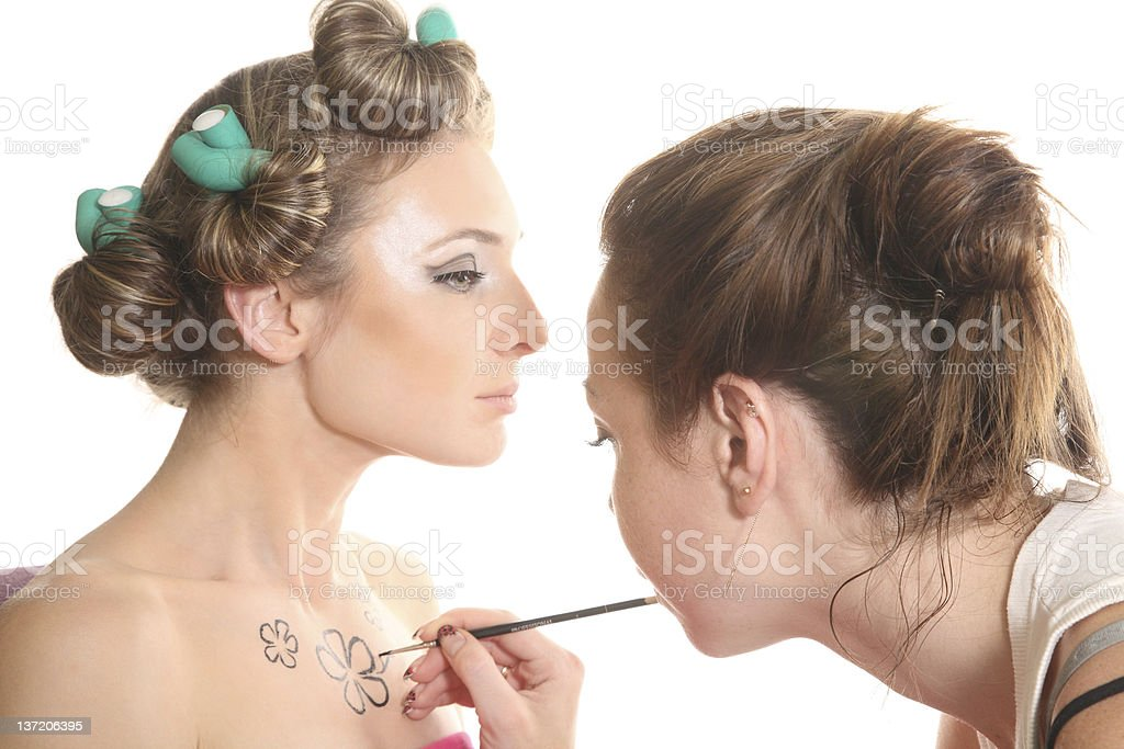 Makeup artist paints body art on the chest fashion model royalty-free stock photo