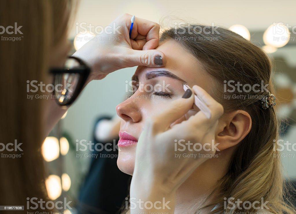 Make-up artist tweezing eyebrow on model's face. stock photo