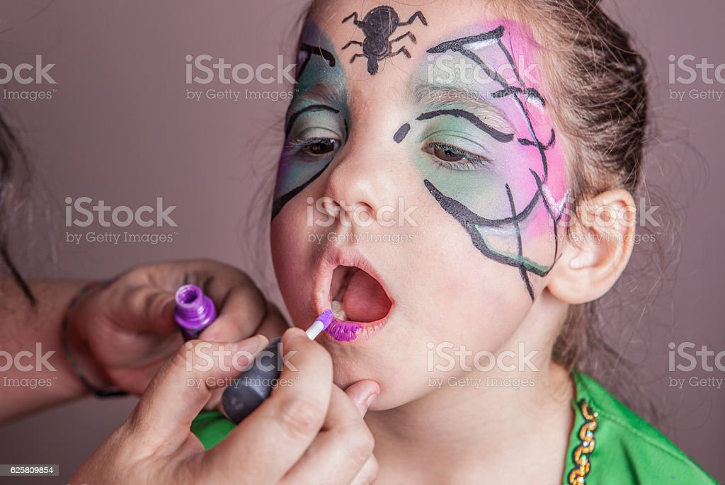 Make-up artist working with a little girl before halloween party stock photo