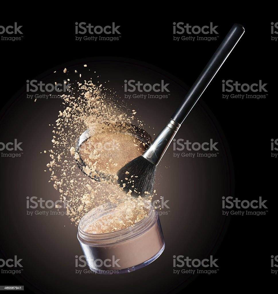 Makeup brush with beige makeup spilling from container royalty-free stock photo