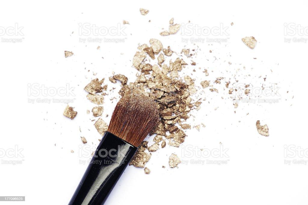 Makeup brush with golden eyeshadow stock photo