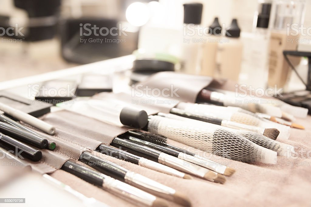 Makeup brushes and cosmetics on table in beauty salon stock photo