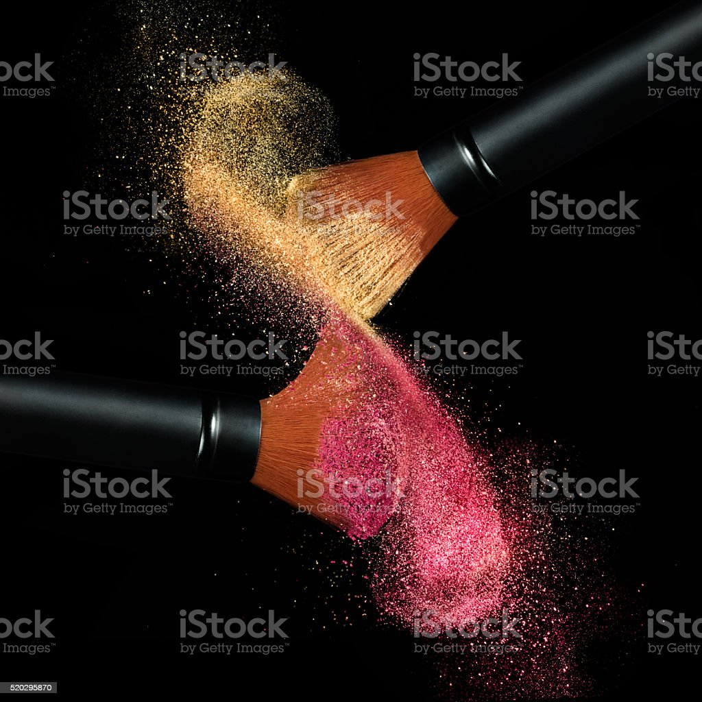 Makeup brushes applying powder isolated on black stock photo