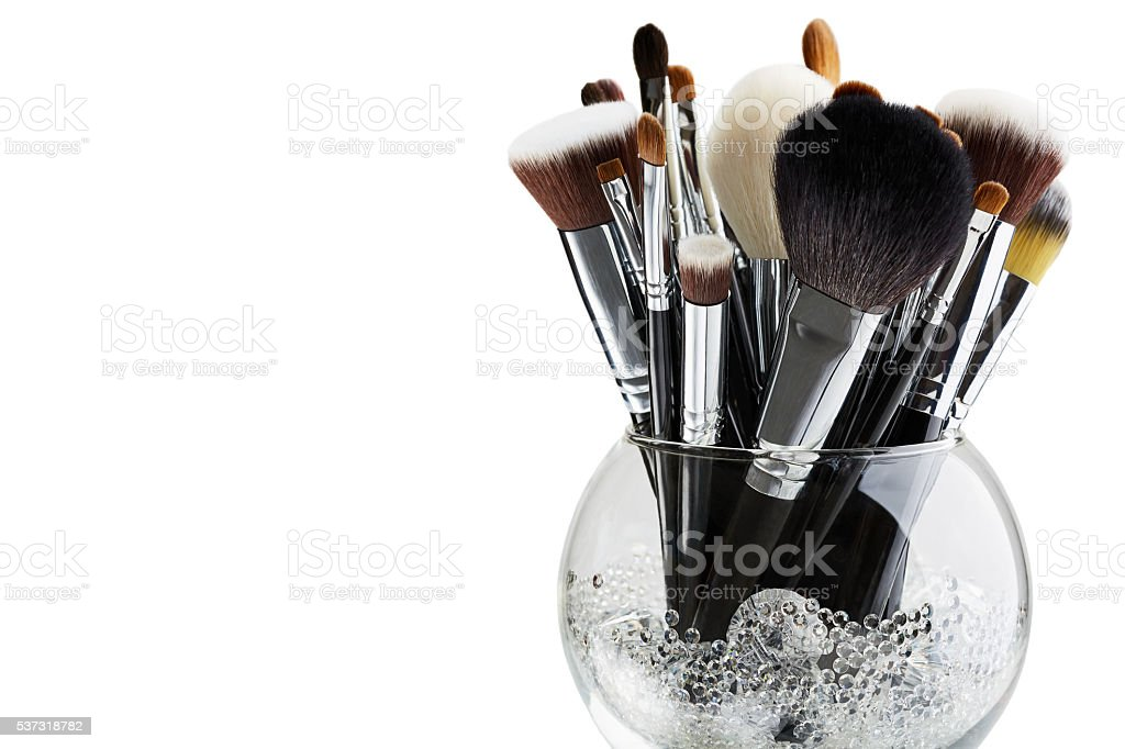Makeup brushes in a glass vase stock photo