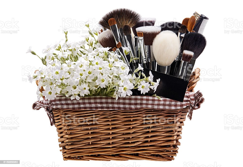 Makeup brushes set in crib with flowers. Chickweed. Isolated. stock photo