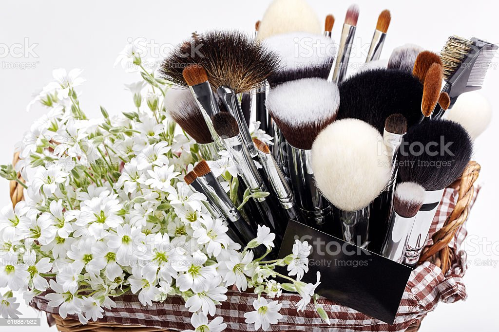 Makeup brushes set in pottle with flowers. Chickweed. stock photo