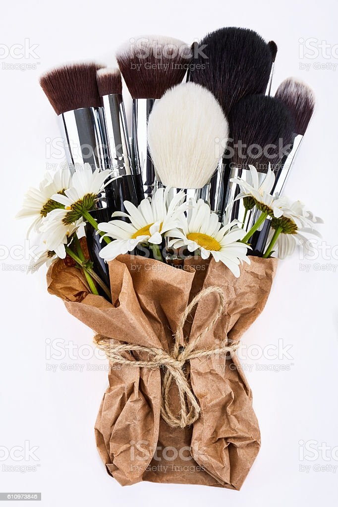 Makeup brushes set packed in paper with chamomiles stock photo