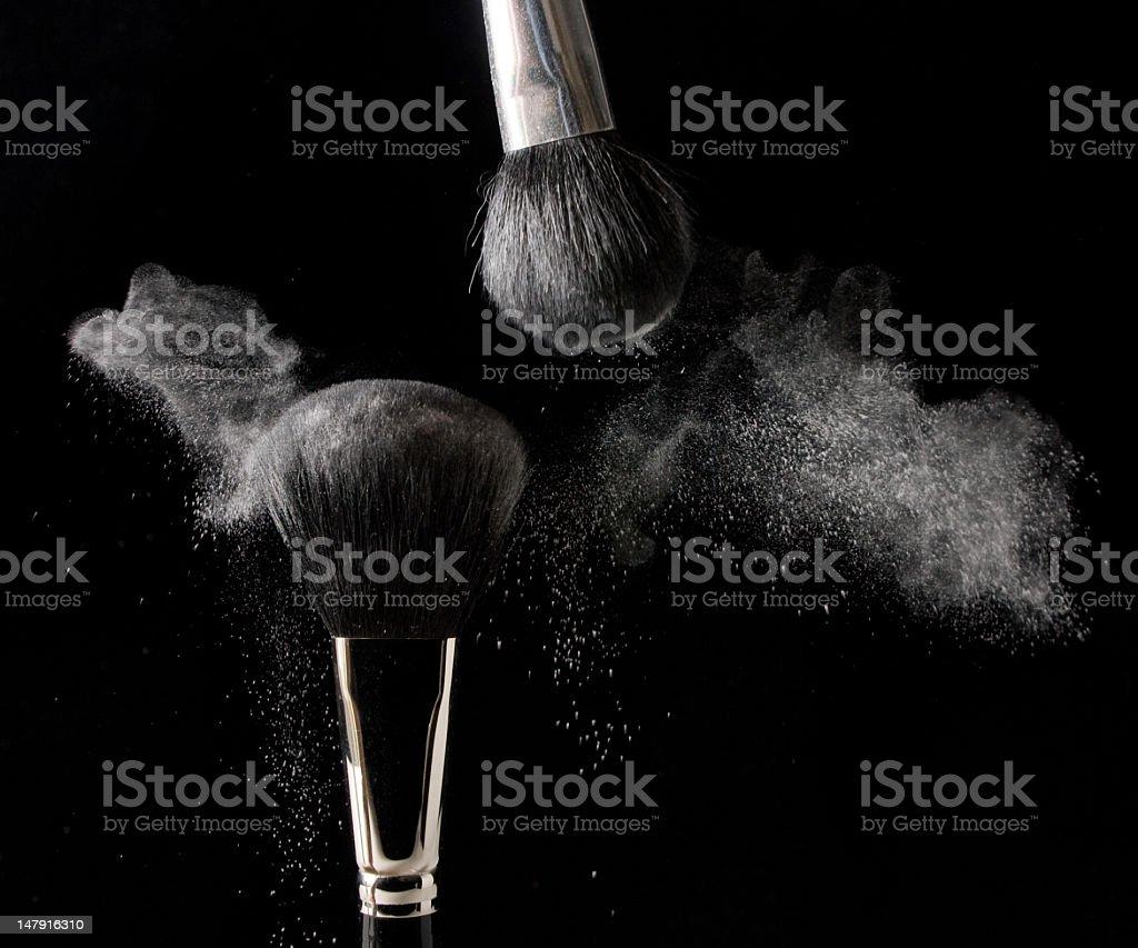 Makeup brushes shaking off powder on black background royalty-free stock photo