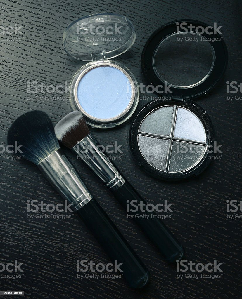 Makeup cosmetics products on wooden black background stock photo