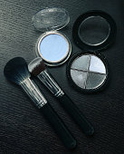 Makeup cosmetics products on wooden black background