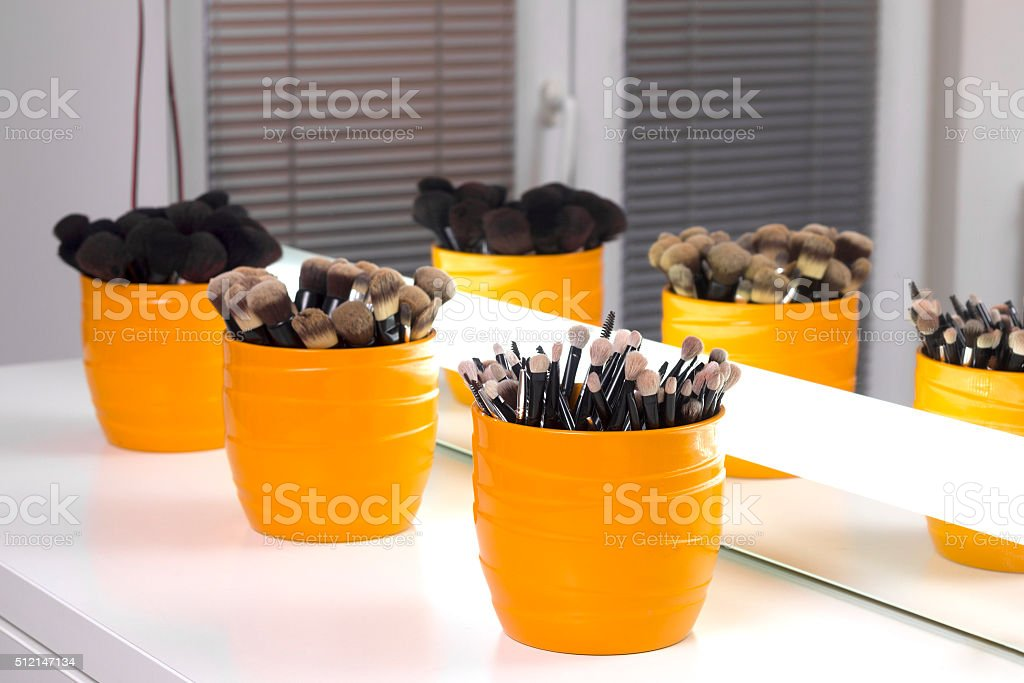 Makeup studio. Collection of makeup brushes in bowl. stock photo