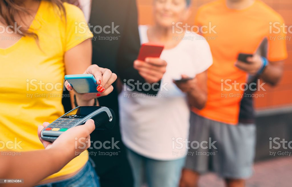 Making a contactless payment with smartphone stock photo