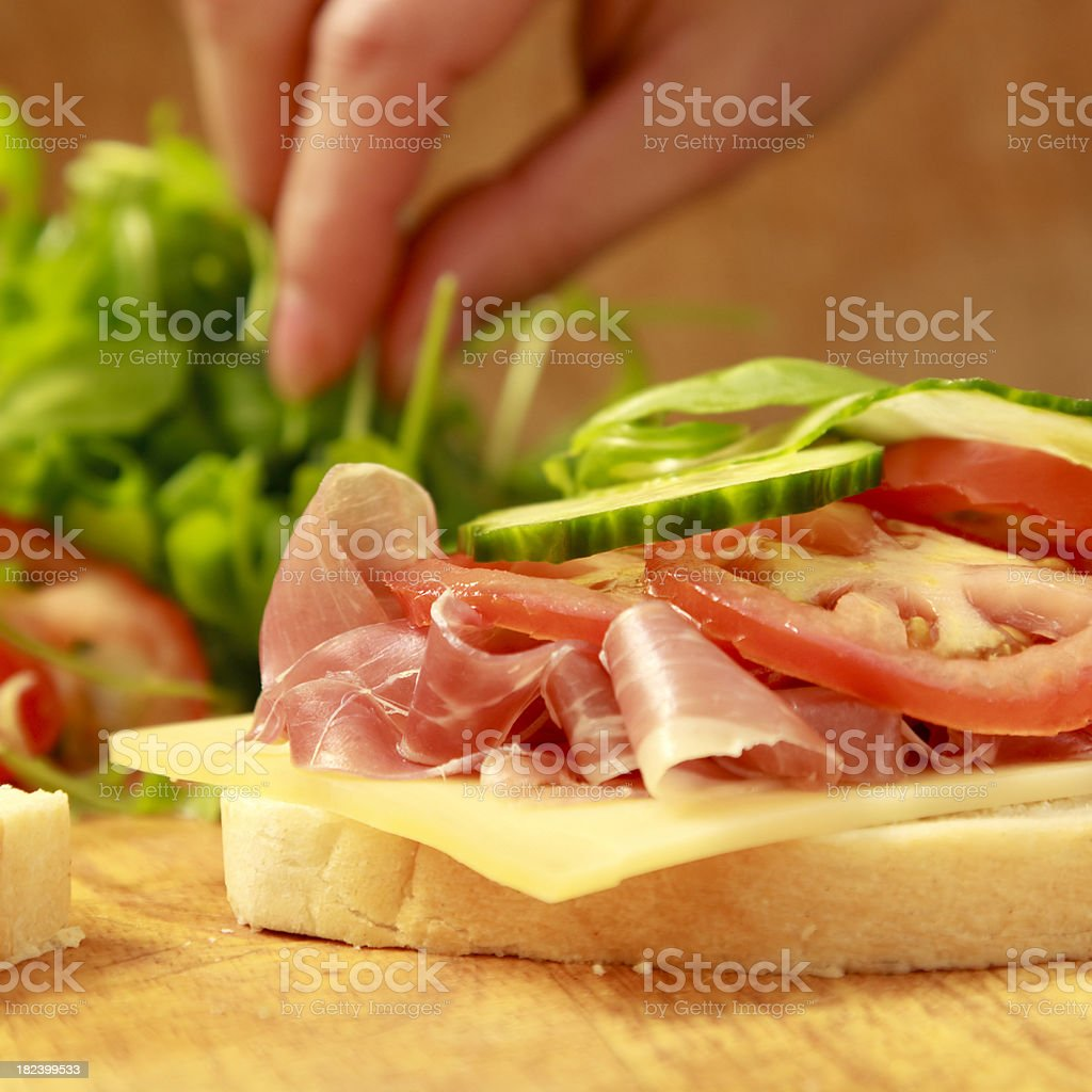 making a ham, cheese and salad sandwich royalty-free stock photo