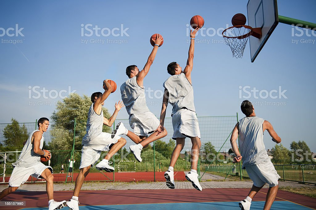 Side view of young male basketbal player scoring, multiple image