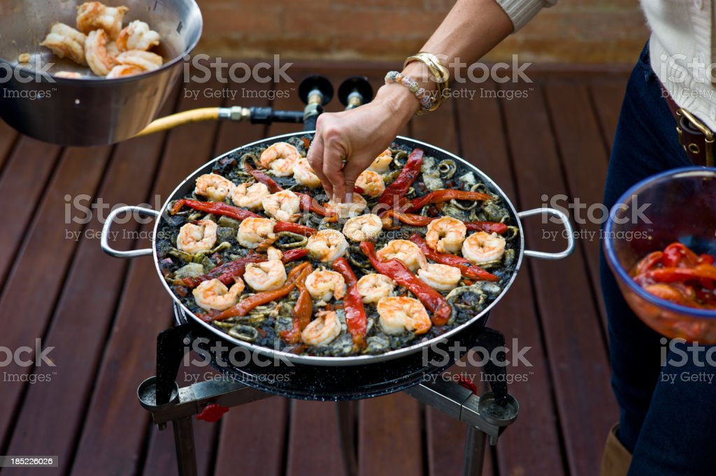 Making Black Paella: Decorating with Grilled Shrimp and Peppers stock photo