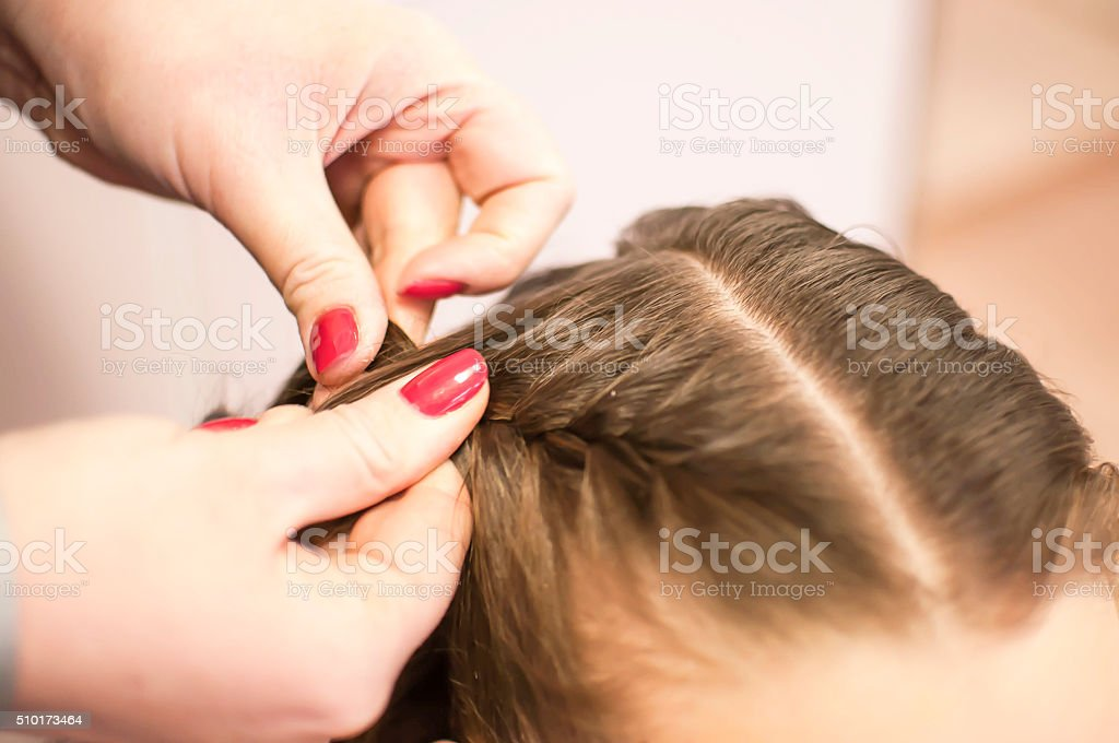 Making braids on the girl's head stock photo