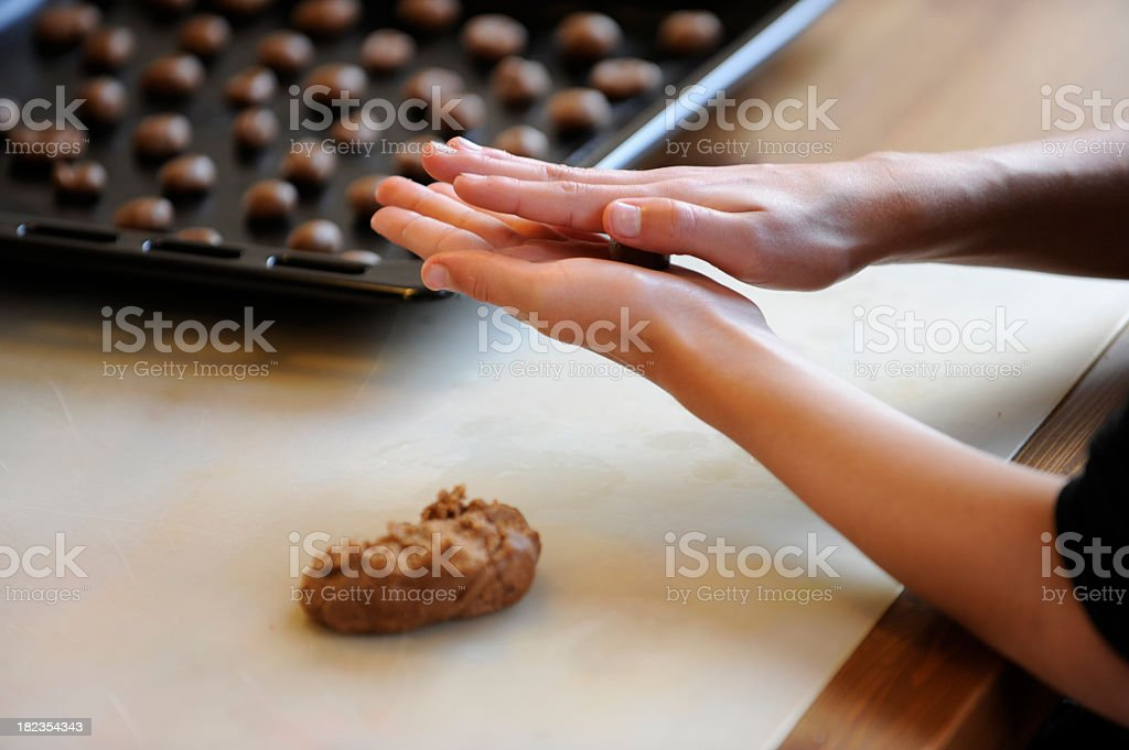 Making brown spiced biscuit or pepernoten with dough stock photo