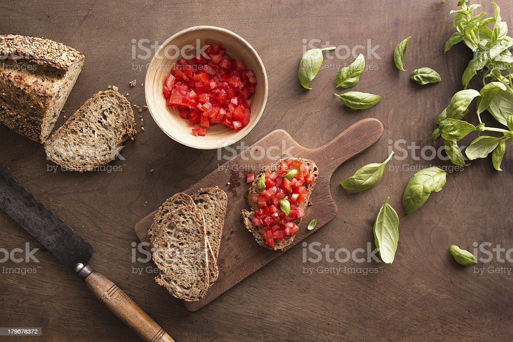 Making bruschetta on wooden table royalty-free stock photo
