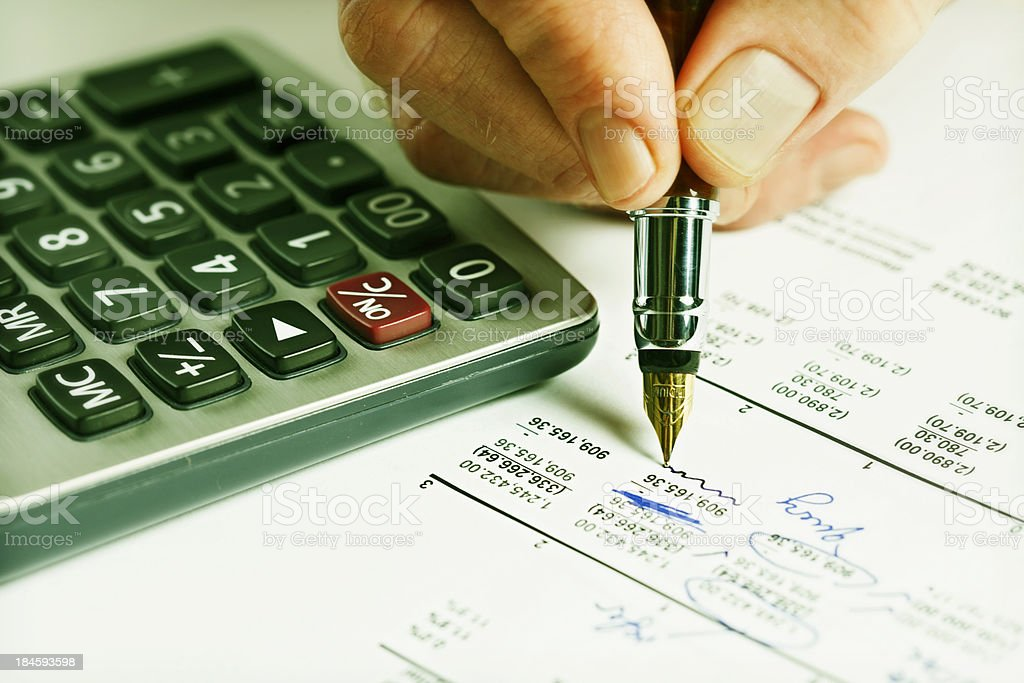 Making corrections to spreadsheet with calculator and fountain pen royalty-free stock photo