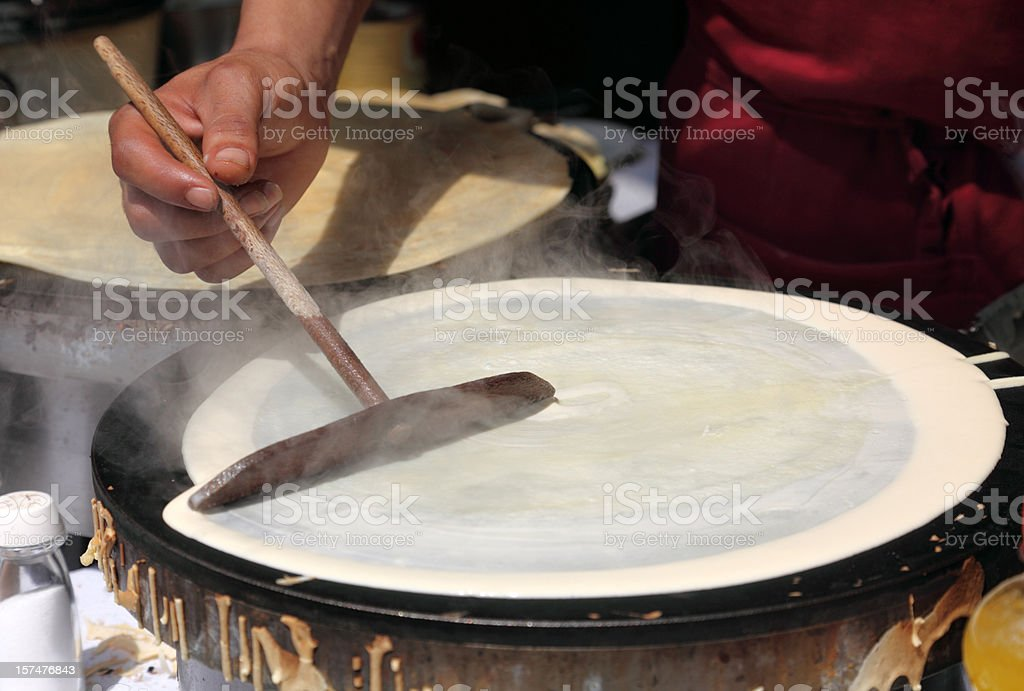 Making crepes on a steaming hot griddle stock photo