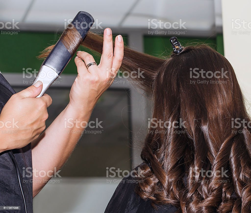 Making curles with hair iron at the hairdressers stock photo