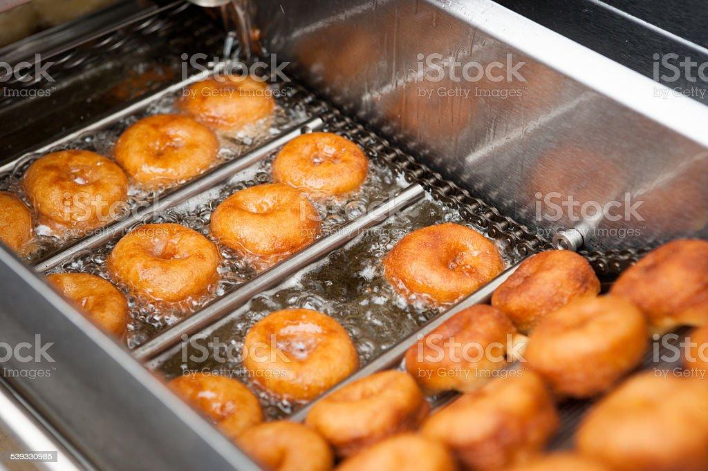 making deep fried doughnuts stock photo
