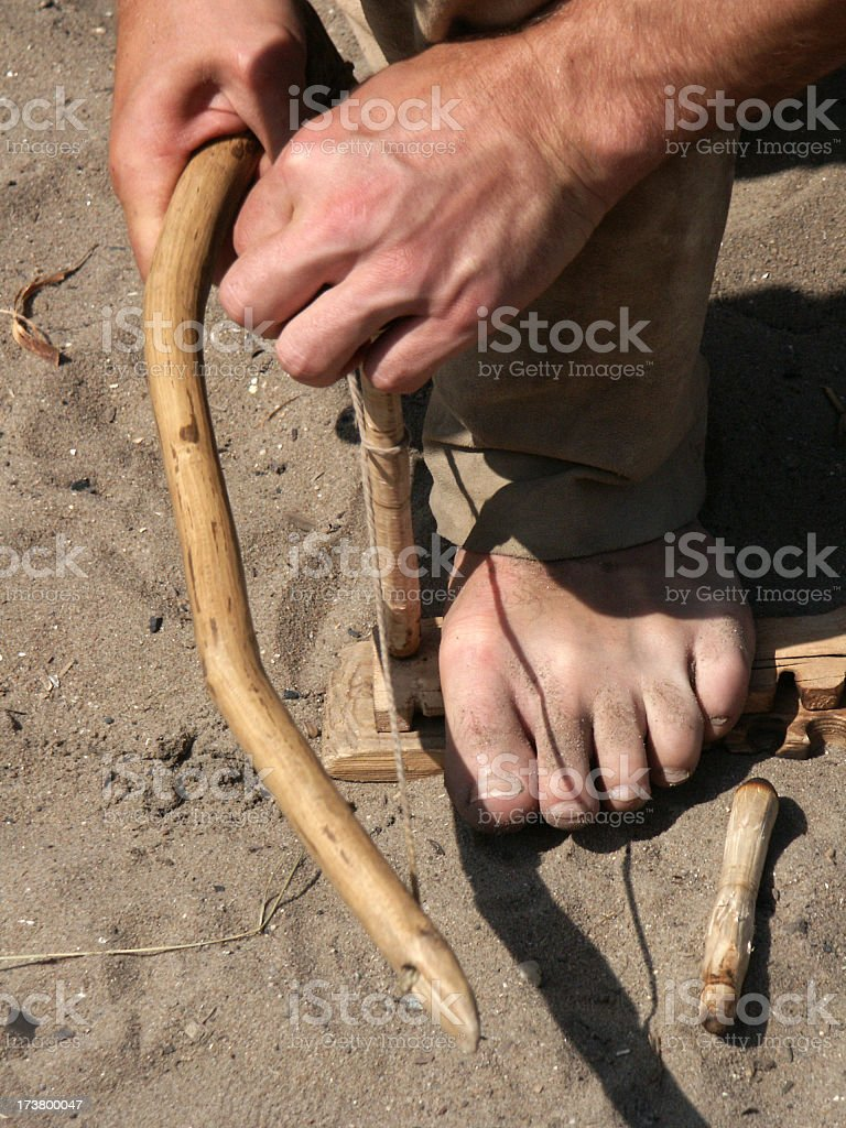 Making fire with handbow hands and foot stock photo