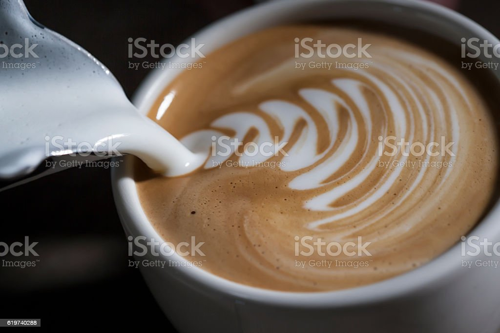 Making latte Art on a Cappucinno. Freshly made stock photo