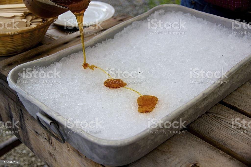 Making maple syrup taffy at the sugar shack stock photo