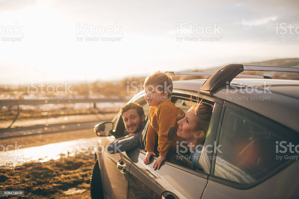 Photo of cute little family during their excursion with family car