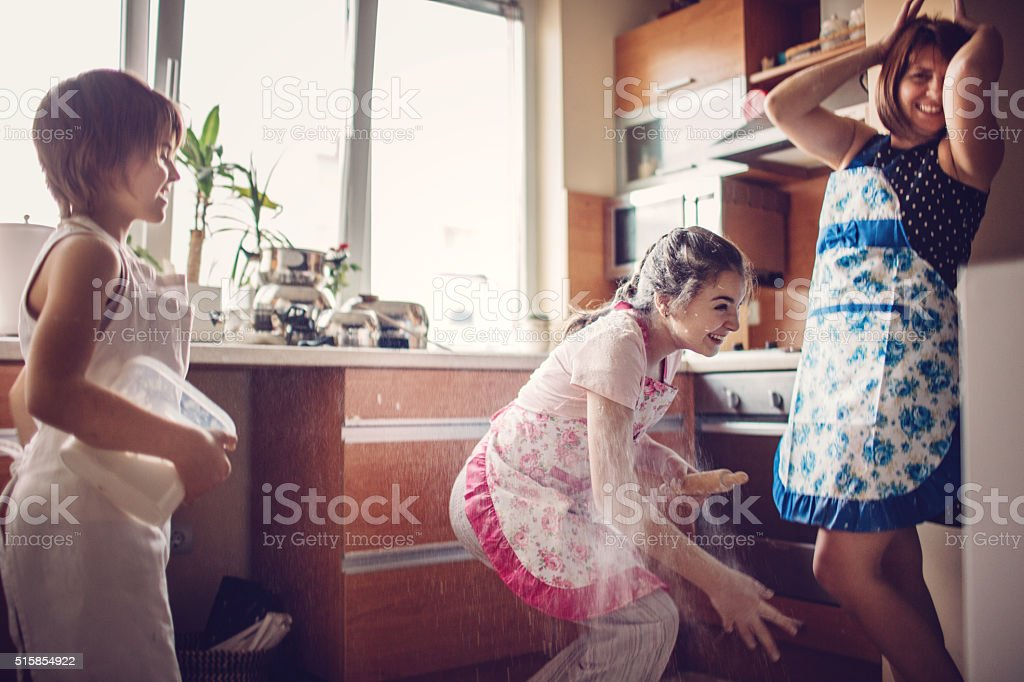Children and their mother having fun throwing flour in the kitchen