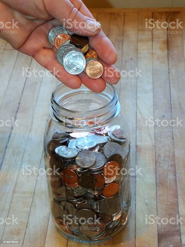 Making My Deposit - Coins into Clear Glass Mason Jar stock photo