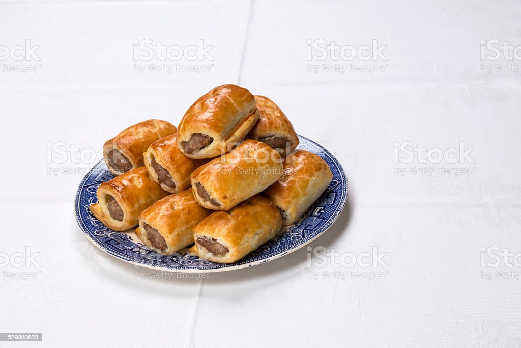 Making sausage rolls, finished sausage rolls on willow pattern plate stock photo