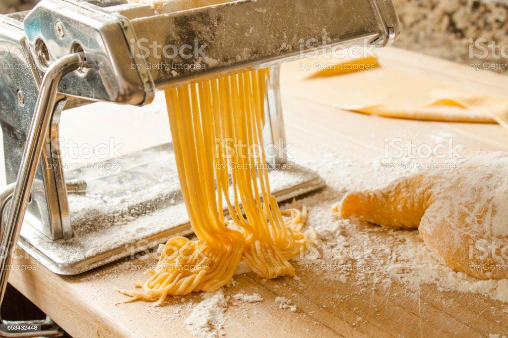 making spaghetti with fresh pasta dough and press machine stock photo