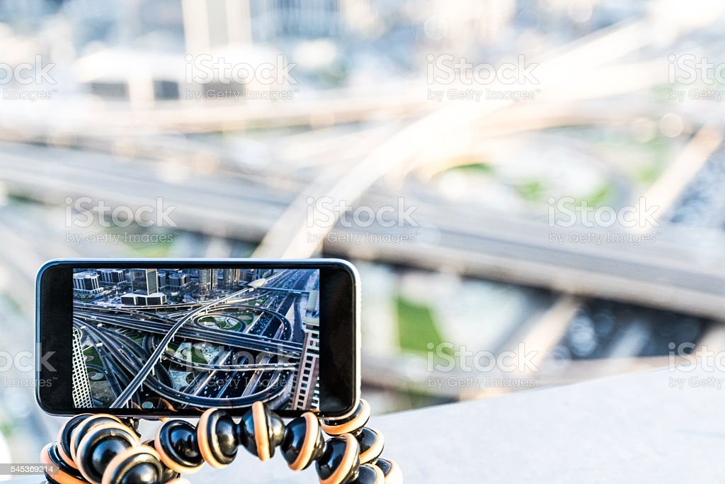 Making timelapses on my smartphone over modern Dubai road system stock photo