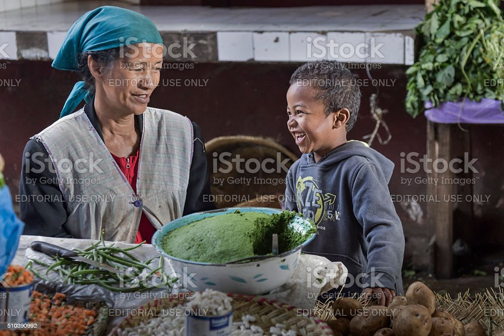 Malagasy kid laughing with his mum in Madagascar market stock photo