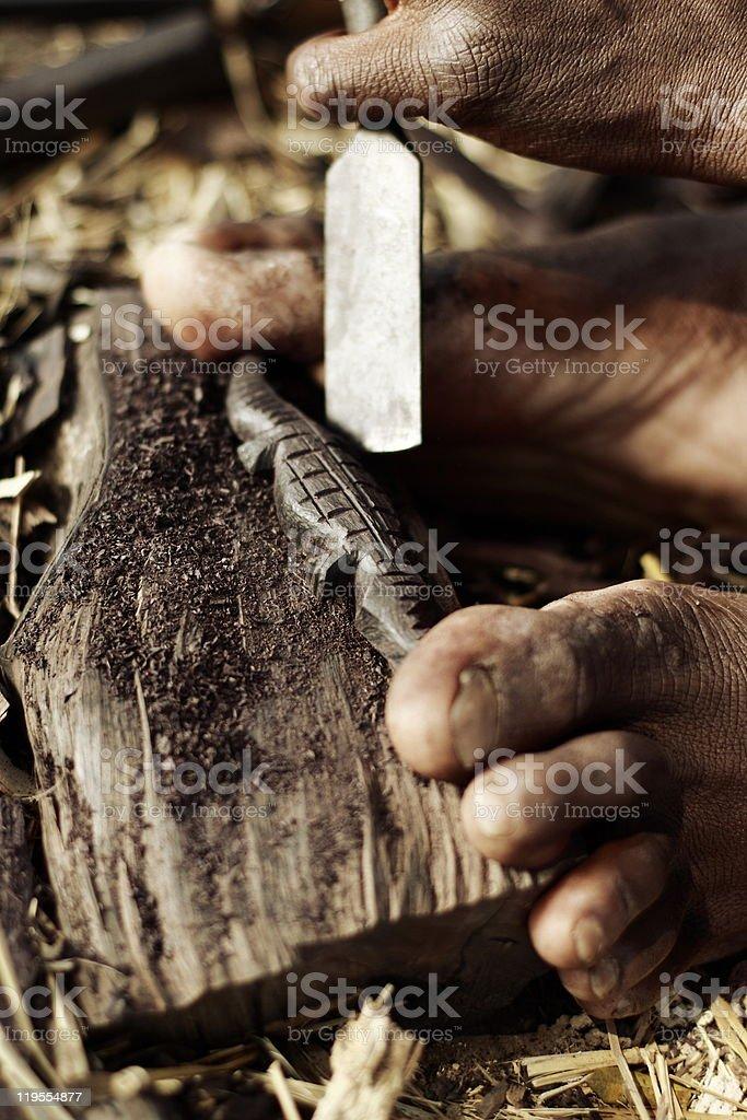 Malawian Carver Making a Wooden Crocodile stock photo