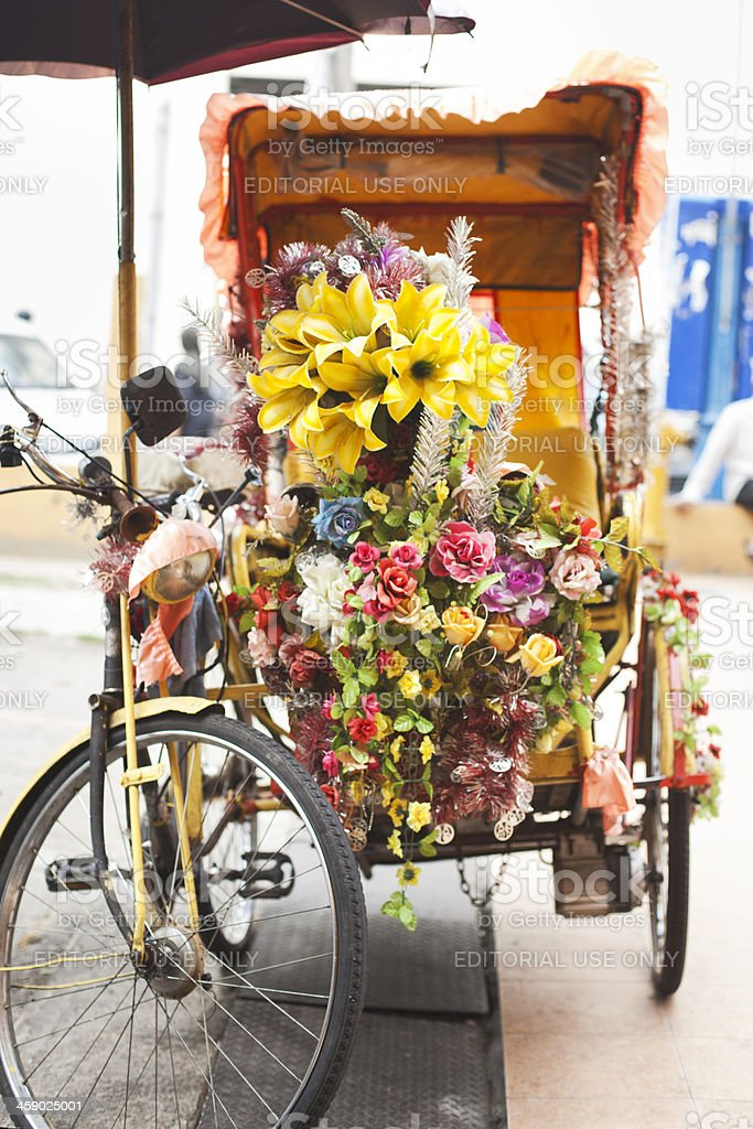 Malay rickshaw decorated with tropical flowers. stock photo