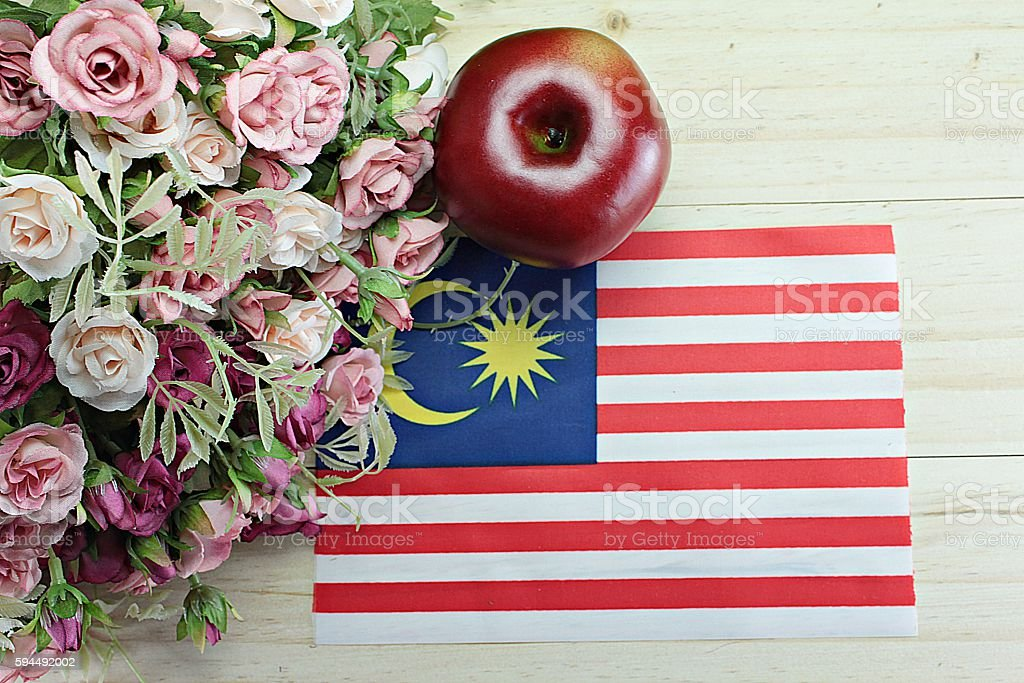 Malaysia flag, apple and flower on wood background stock photo