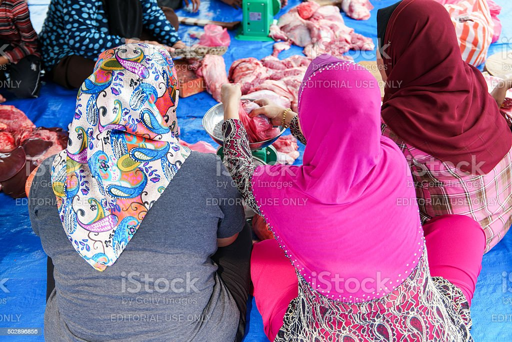 Malaysian Muslims help in halal slaughtering part of cow. stock photo