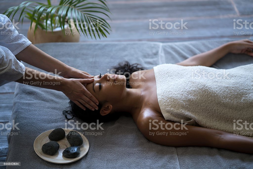 Malaysian woman receiving head massage at the spa. stock photo